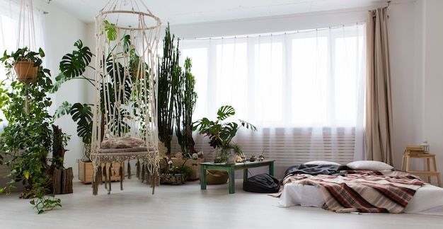 Interior of a modern studio apartment with lots of plants and a bed on the floor Premium Photo