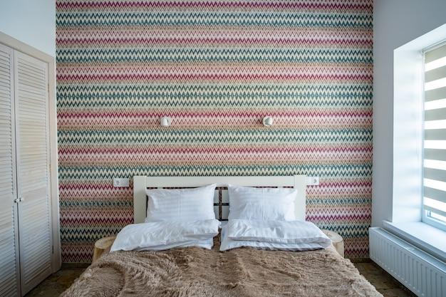 Интерьер просторной спальни отеля со свежим бельем на большой двуспальной кровати. уютный современный номер в современном доме. Premium Фотографии