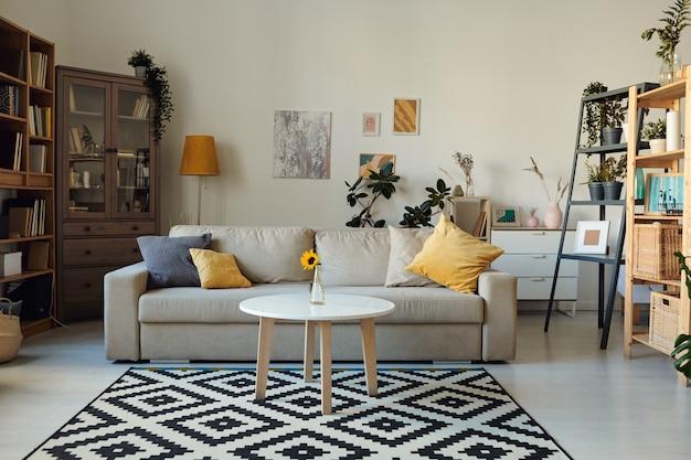 벽, 책장, 베개가있는 소파 및 꽃병이있는 커피 테이블에 그림이있는 아늑한 거실의 인테리어 프리미엄 사진