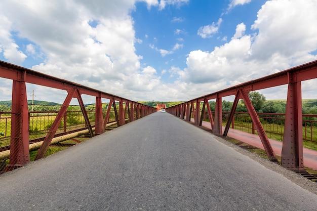 Интерьер структуры металла моста в солнечном дне. перспектива до бесконечности у моста в украине Premium Фотографии