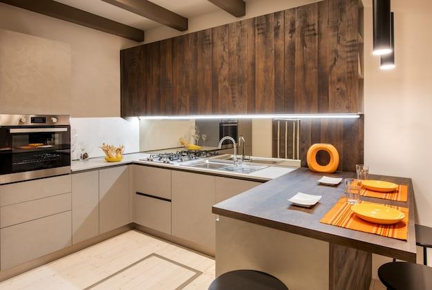 오렌지색으로 강조된 현대적인 주방 인테리어와 매입 형 조명이있는 중성 베이지 색 캐비닛 프리미엄 사진