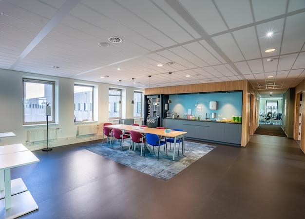 Интерьер кухонной зоны современного офиса с длинным деревянным столом и стульями Бесплатные Фотографии