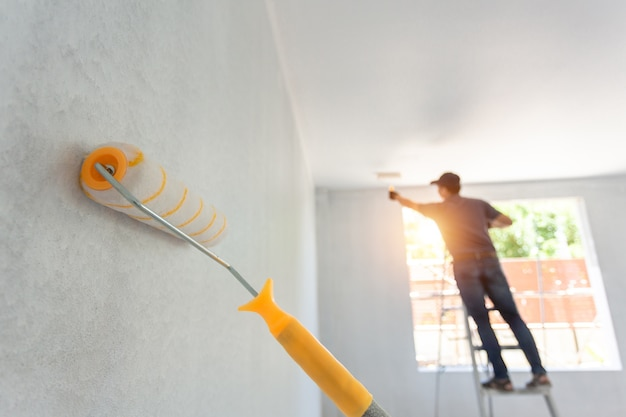 Interior painting roller and the worker in the background. home remodeling concept. Premium Photo
