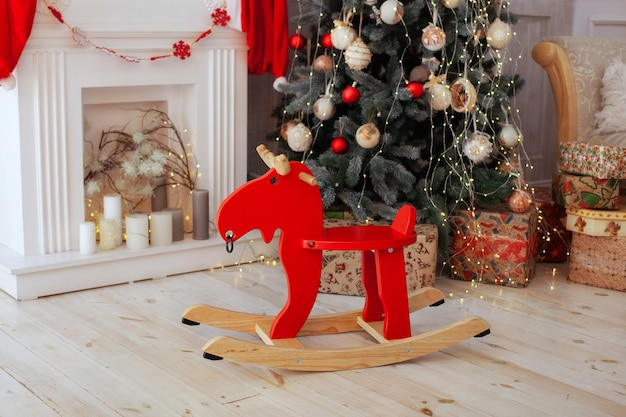 Interior room with wooden elk rocking chair and christmas tree Premium Photo
