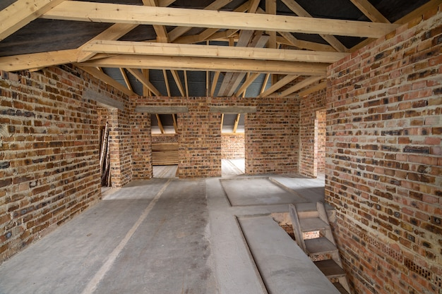 Premium Photo | Interior of unfinished brick house with concrete floor,  bare walls ready for plastering and wooden roofing frame attic under  construction.