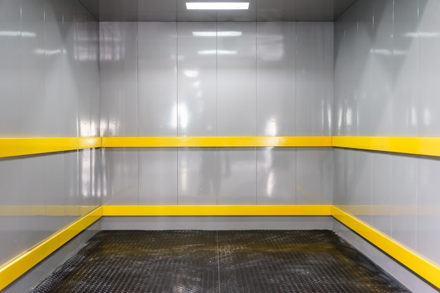 Interior view of a modern industrial elevator facing the back wall Premium Photo