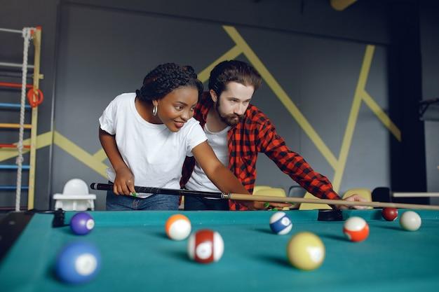 International couple playing a billiard in a club Free Photo