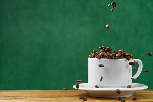 Международный день кофе концепции. крупным планом белая кофейная чашка, полная кофейных зерен. кофейные зерна попадают в белую кружку Premium Фотографии