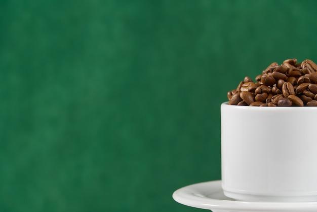 コーヒーのコンセプトの国際デー。緑色の背景でコーヒー豆の完全なクローズアップの白いコーヒーカップ。 Premium写真