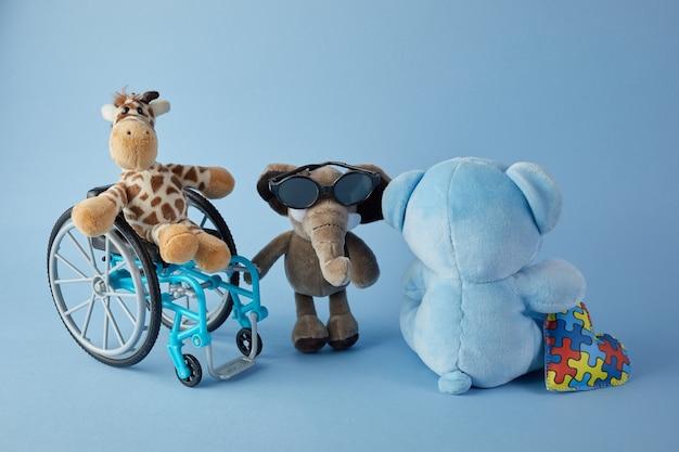 국제 장애인의 날. 파란색 배경에 다른 장애의 장난감 기호 휠체어. 프리미엄 사진