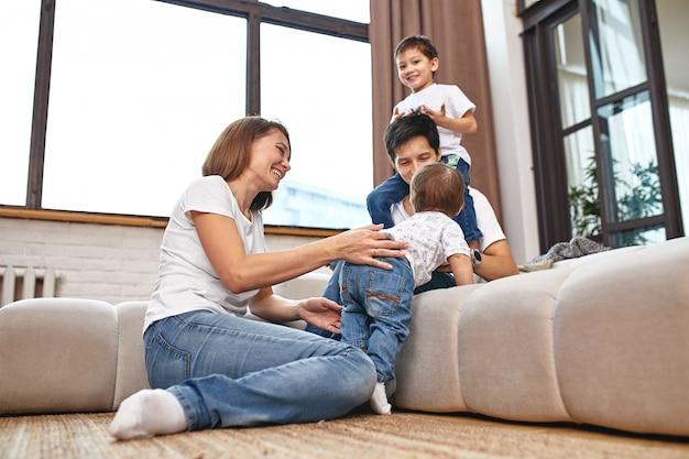 Международная семья дома на диване, обнимаюсь и наслаждаюсь жизнью. счастливая семейная жизнь Premium Фотографии