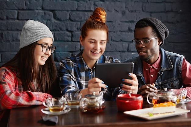 カフェに座ってタブレットを使用してオンラインでビデオを見ている3人の友人の国際的なグループ 無料写真