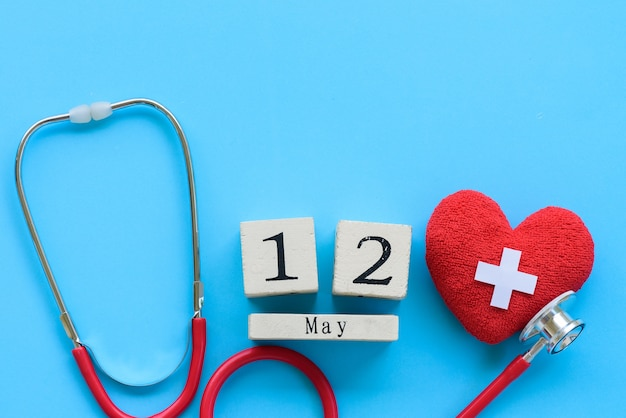 International nurses day, may 12. red heart with stethoscope on blue background. Premium Photo