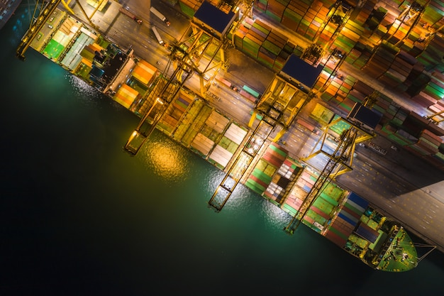 International sea freight station by large cargo containers ship above view frome drone camera at night Premium Photo