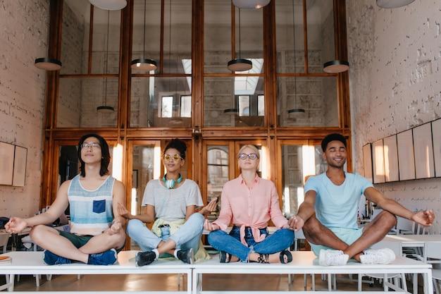 図書館の机で瞑想し、試験前にリラックスする留学生。目を閉じてテーブルでヨガをしている大学の友達。 無料写真