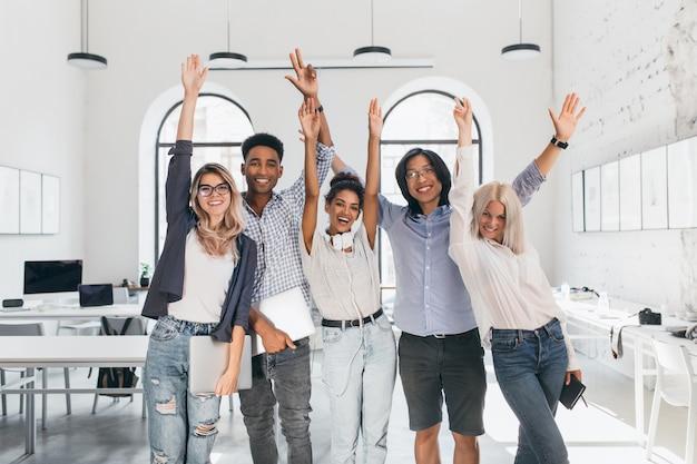 Studenti internazionali stanchi che festeggiano la fine degli esami e ridono in aula. felici programmatori freelance che hanno fatto un lungo progetto e in posa con un sorriso, tenendo in mano laptop. Foto Gratuite
