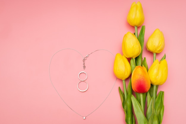 International women's day with flowers and heart shape necklace on pink background Premium Photo