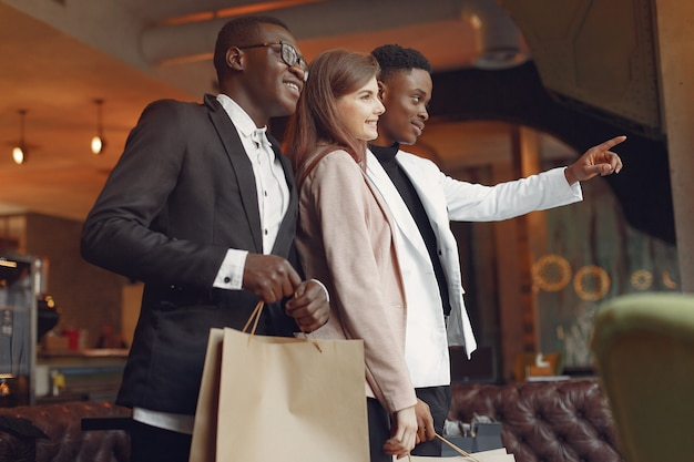 Gente internazionale in piedi in un caffè con le borse della spesa Foto Gratuite