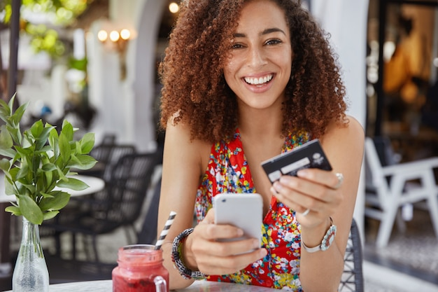 Internet banking and ecommerce concept. happy young smiling female with afro hairstyle, uses modern cell phone and credit card for online shopping Free Photo