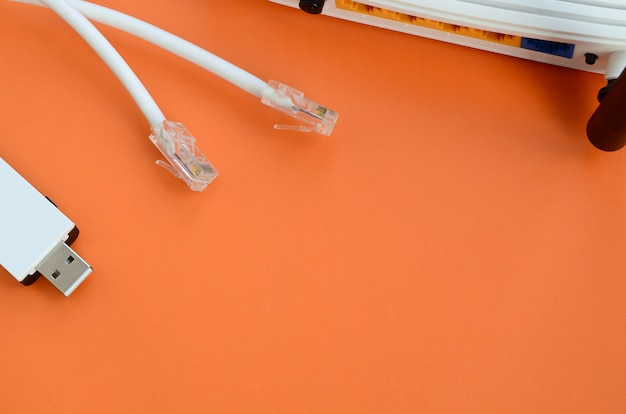 Internet router, portable usb wi-fi adapter and internet cable plugs lie on a bright orange background. Premium Photo