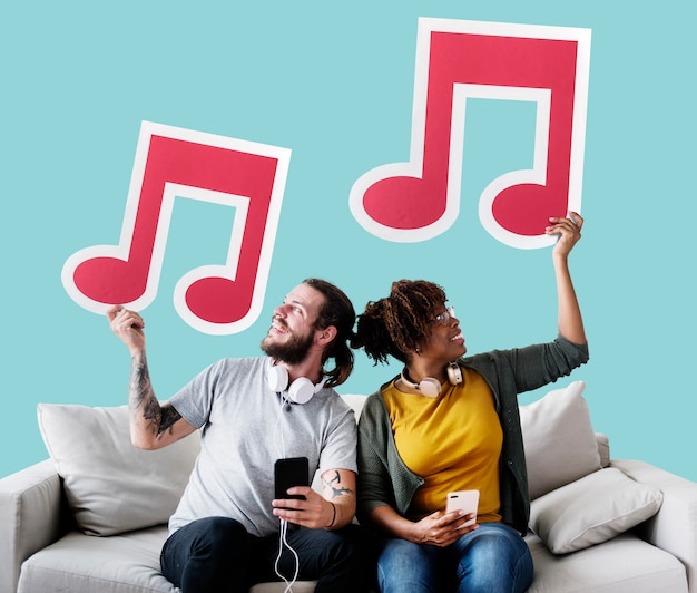 Interracial couple on a couch holding musical notes Free Photo