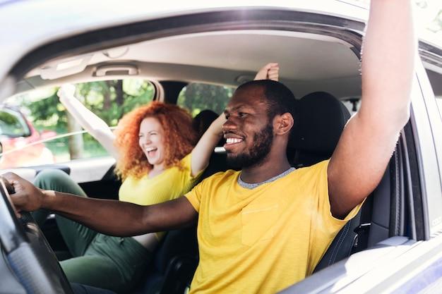 Interracial couple having fun on a car trip Free Photo