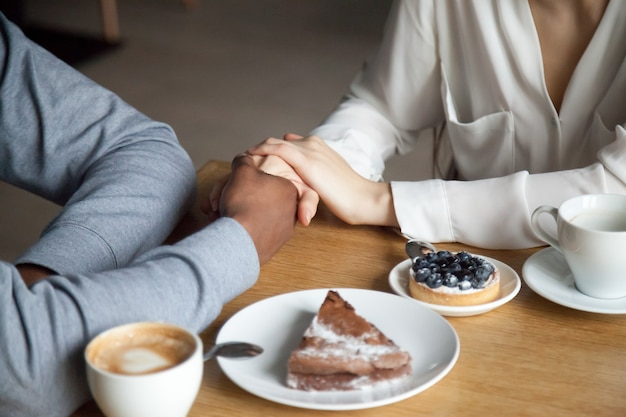 Interracial couple holding hands sitting at cafe table, closeup view Free Photo