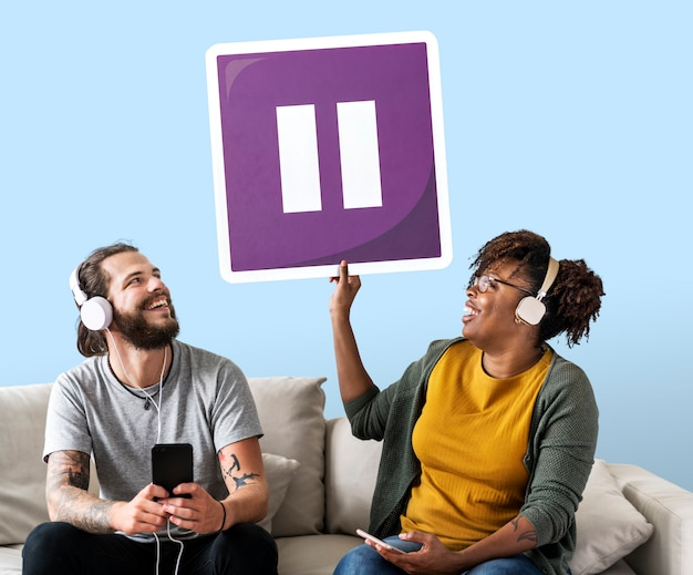 Coppie interrazziali che ascoltano la musica e che tengono un bottone di pausa Foto Gratuite