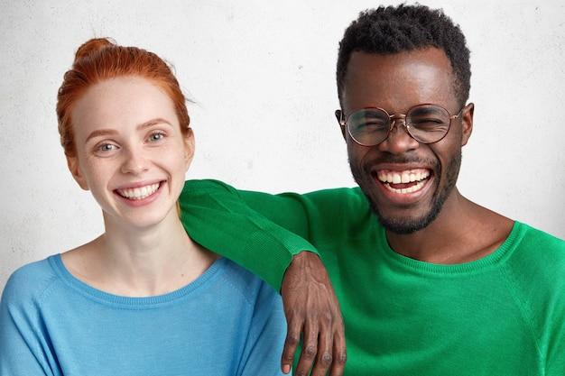 Межрасовые подруги-мужчины и девушки веселятся вместе: смуглый мужчина смеется над хорошей шуткой Бесплатные Фотографии