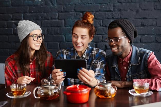 Межрасовая группа из трех хипстеров, использующих тачпад в кафе Бесплатные Фотографии