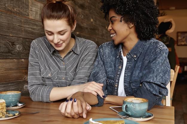 カフェでリラックスした異人種間の幸せなレズビアンカップル 無料写真