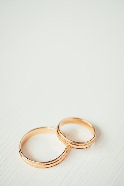 Intersecting wedding gold rings at the bottom of the white wooden background Premium Photo
