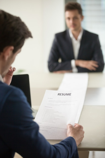 Interviewer reading applicants long resume Free Photo