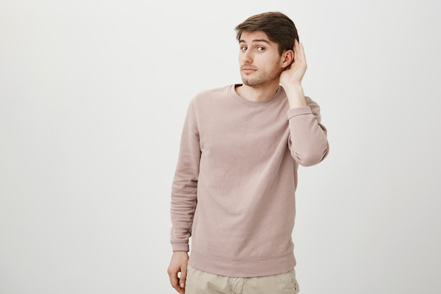 Intrigued cute guy eavesdropping, hold hand near ear Free Photo