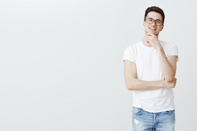 Ragazzo intelligente incuriosito con gli occhiali che pensa, vedi una scelta interessante Foto Gratuite