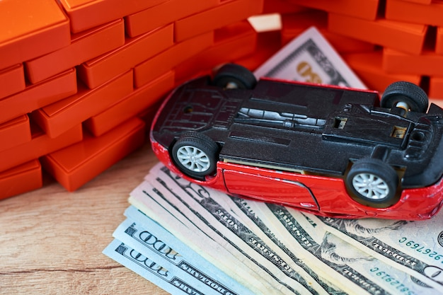 Inverted car on pile of a dollar bills.  concept of car insurance, damages after the accident Premium Photo
