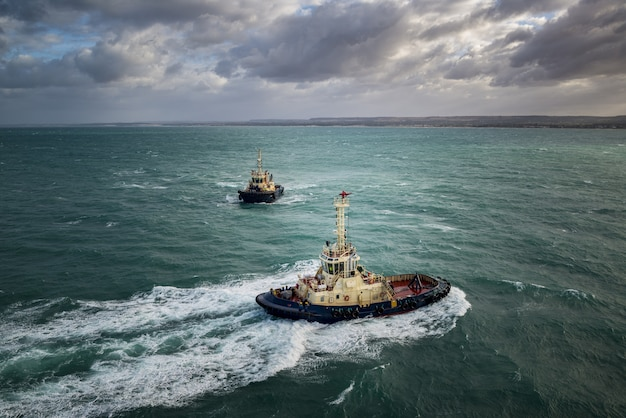 Следственные катера плывут в бирюзовом океане под пасмурным небом Бесплатные Фотографии