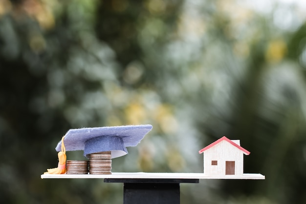 Investment and education saving ideas: dropshipping money coins to graduation cap on wood balance with house model. concept of educate university requires saving moneys, will bring home degree. Premium Photo