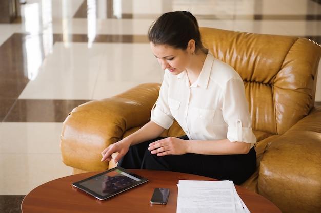 座っている間ipadに取り組んで忙しいビジネスの女性の肖像画 Premium写真