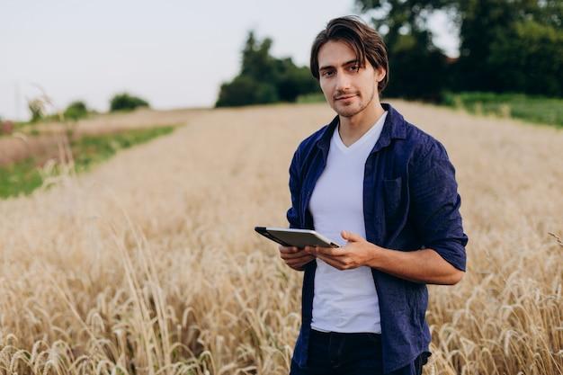 Ipadと麦畑に立っている笑顔若い農学者の肖像画 Premium写真