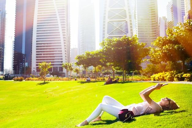 明るい夏の太陽が緑の芝生に横たわっている女性の上に光り、公園で彼女のiphoneをチェックする 無料写真