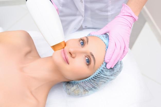 アンチエイジング手順。スキンケアのコンセプト。化粧品クリニックで色素沈着を除去する顔の美容治療を受けている女性。強力なパルス光療法。 ipl。若返り、フォトフェイシャルセラピー。 Premium写真