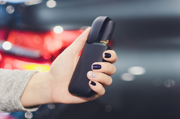 Iqos heat-not-burn tobacco product technology. woman holding e-cigarette in his hand before smoking. Premium Photo