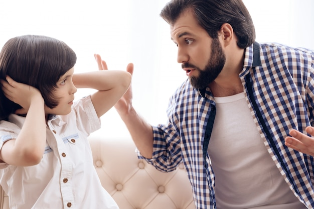 Irate father scolds teenage son which plugs ears. Premium Photo