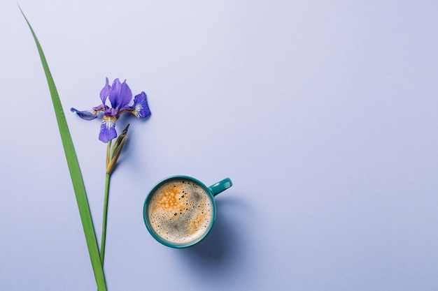 Iris blueflag flower with cup of coffee over purple surface Free Photo