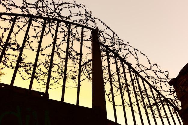 Железные ворота с колючей проволокой Premium Фотографии