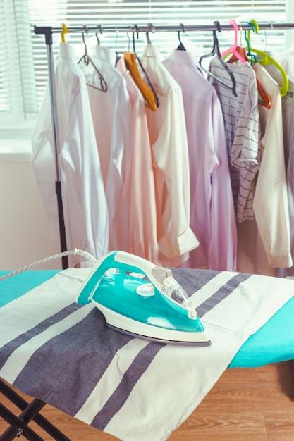 Iron on ironing board on light home interior Premium Photo