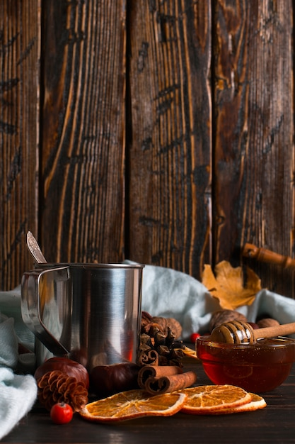 Iron mug with black coffee, honey, spices, on a background of a scarf, dry leaves on a wooden table. autumn mood, a warming drink. copyspace. Premium Photo