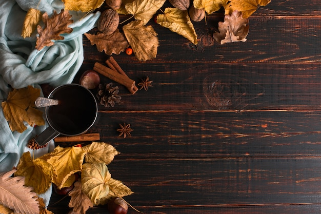 Iron mug with black coffee, spices, on a background of a scarf, dry leaves on a wooden table. autumn mood, a warming drink. copyspace. Premium Photo