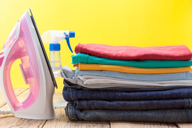 Iron and stack of colored clothes yellow background Premium Photo